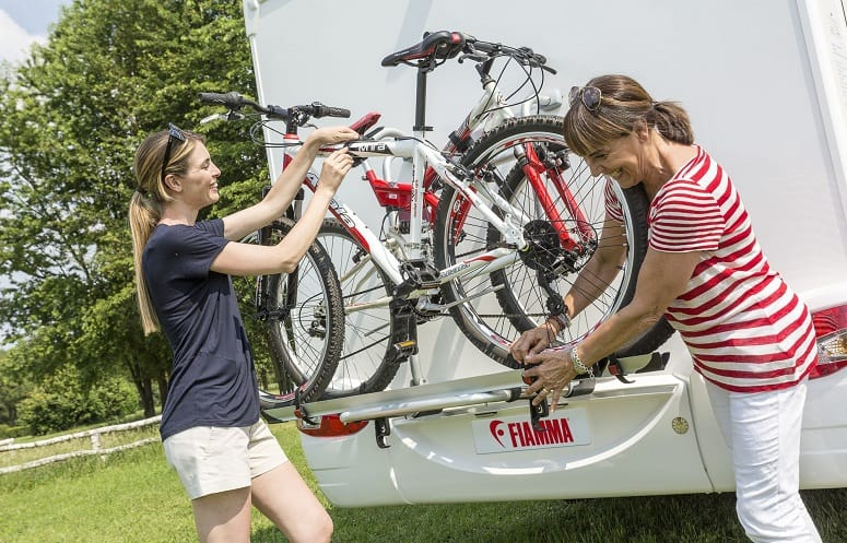 Two Women Mounting Bikes On RV Bike Rack