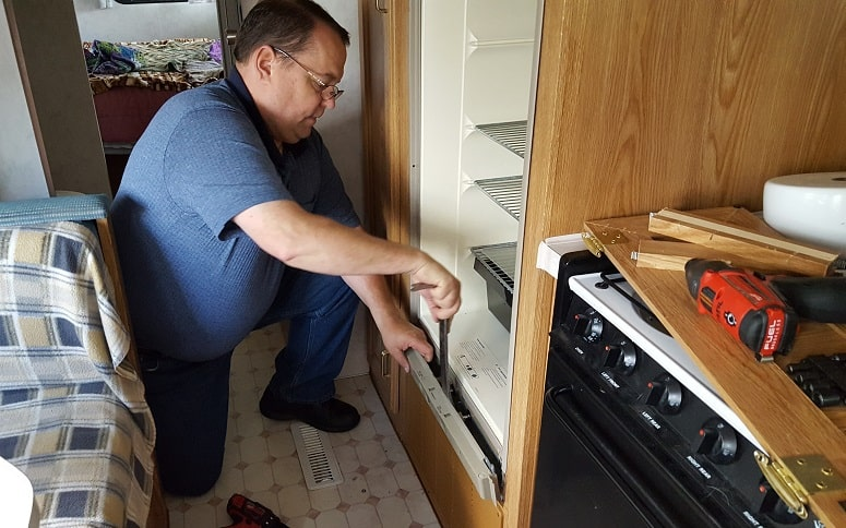 Man Trying To Fix RV Fridge