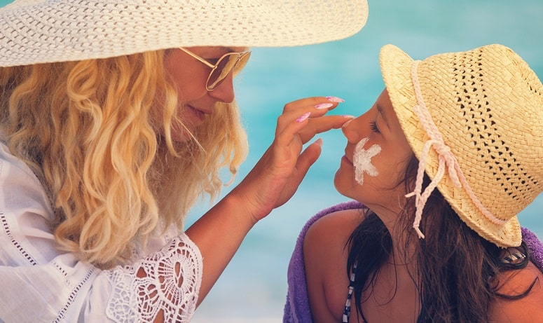 Mom And Daughter Applying Sun Lotion