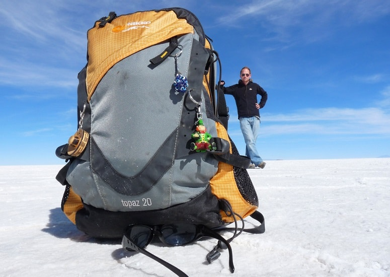 Man Standing Next To Backpack