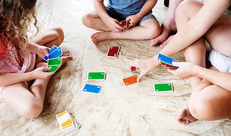kids playing with cards while camping outside