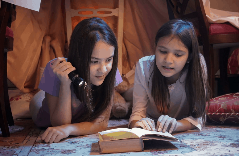 Two Girls Reading Book With Flashlight Turned On