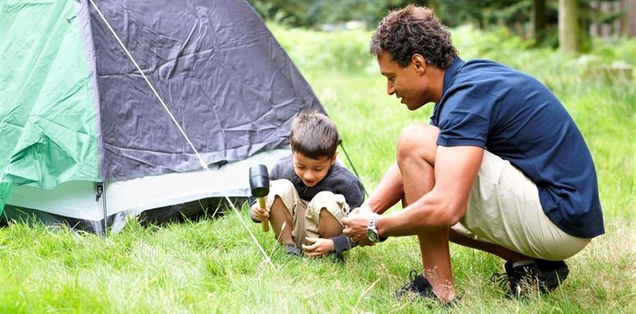 setting up a tent with your kid while camping